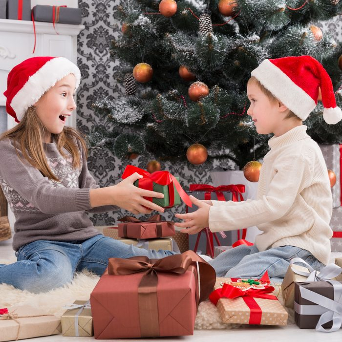 Cute happy excited children, boy and girl in santa hats unwrap christmas present.