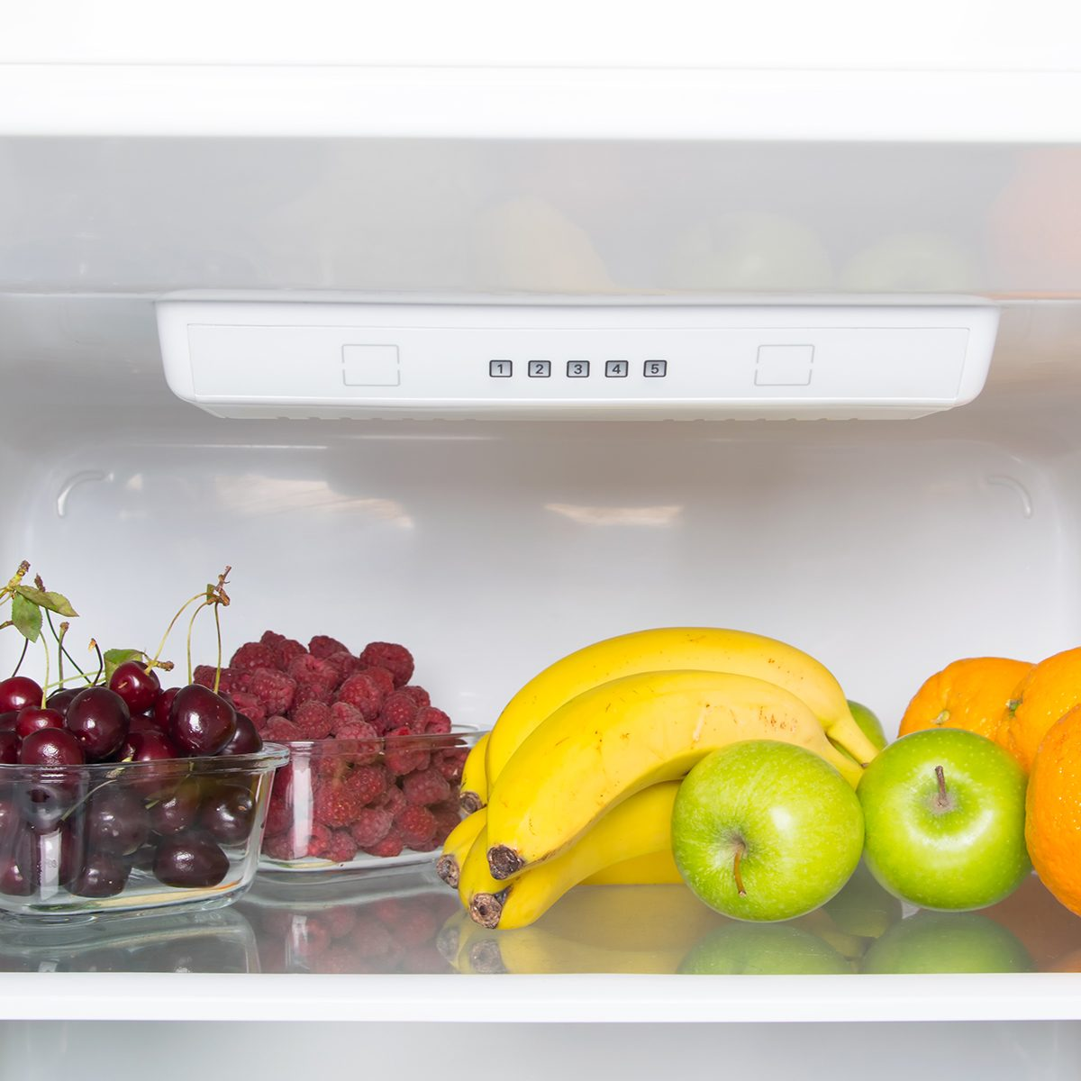White refrigerator shelf close-up, fruits and berries, raspberries and cherries
