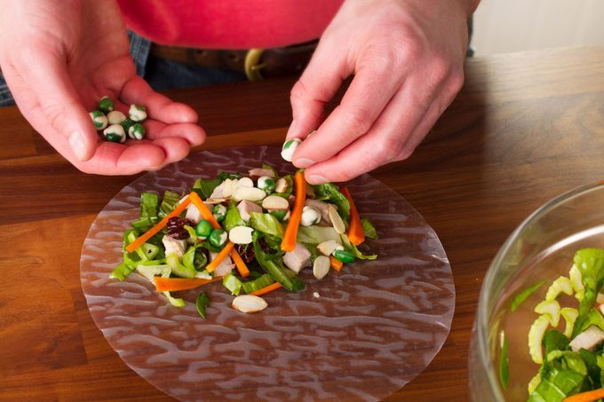 A person filling a spring roll wrapper with fresh vegetables.