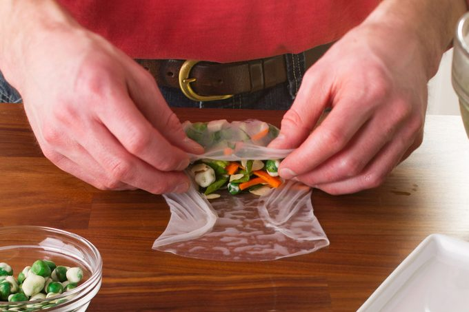 A person wrapping homemade spring rolls.