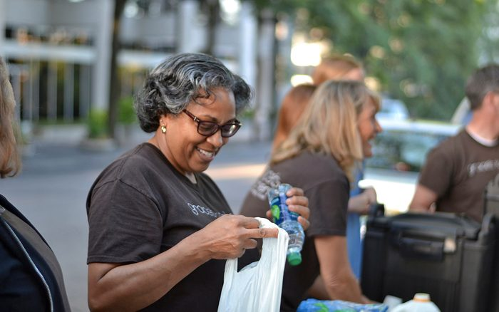 Woman putting water bottle in plastic bag while smiling