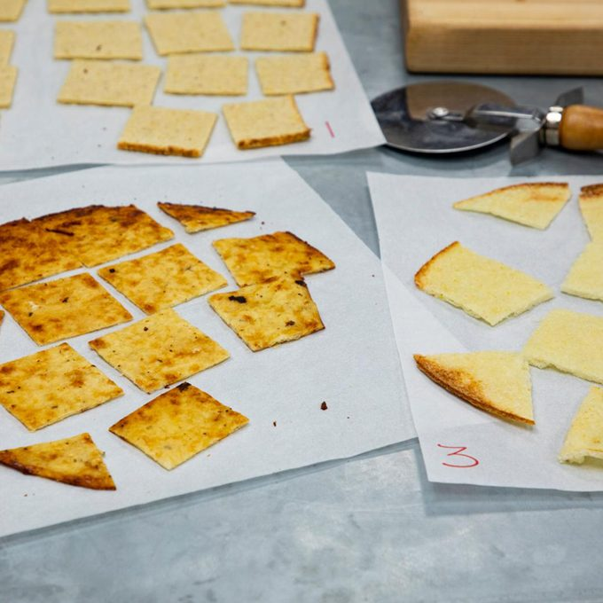 three parchment sheets of cut up cauliflower crusts