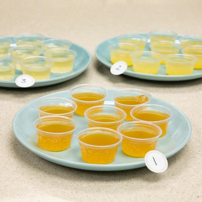several small cups on kombucha on three blue plates