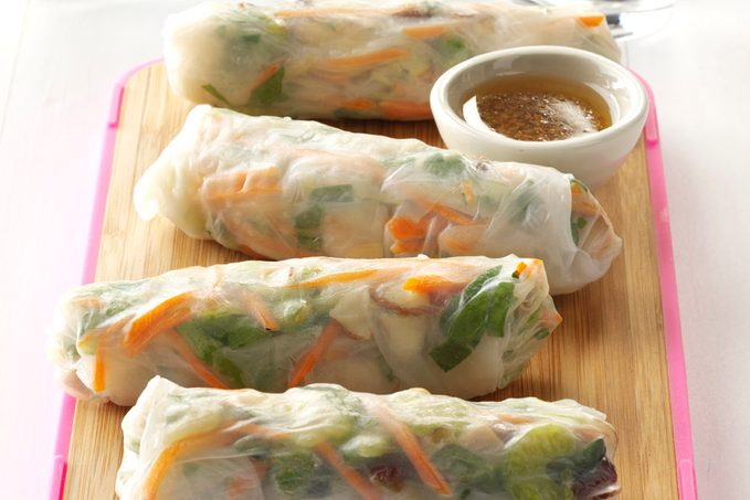 Four homemade spring rolls arranged on a cutting board with a bowl of dipping sauce.