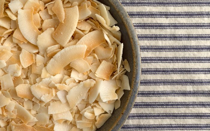 Top close view of a stoneware bowl filled with toasted coconut flakes on a blue and white striped tablecloth.