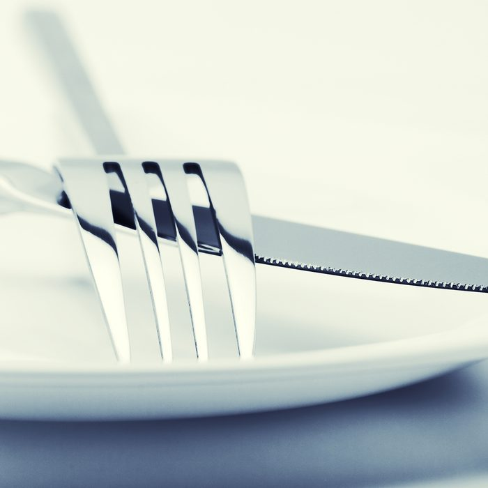 White plate, fork and knife on light background. Toned image.