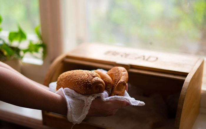 woman taking a bread loaf from a bread box in the kitchen at home