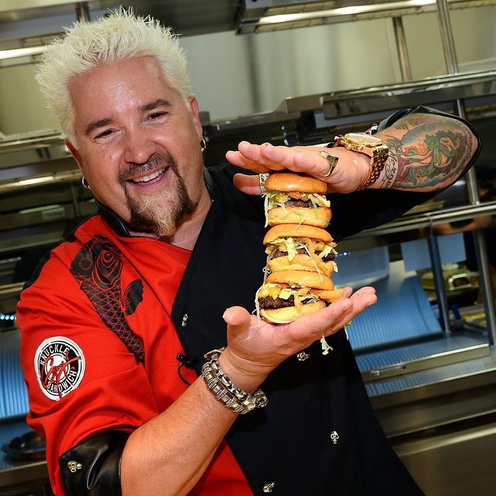 LAS VEGAS, NV - APRIL 04: Chef and television personality Guy Fieri holds hamburgers in the kitchen during a welcome event for Guy Fieri's Vegas Kitchen & Bar at The Quad Resort & Casino on April 4, 2014 in Las Vegas, Nevada. The restaurant opens on April 17. (Photo by Ethan Miller/Getty Images for Caesars Entertainment)