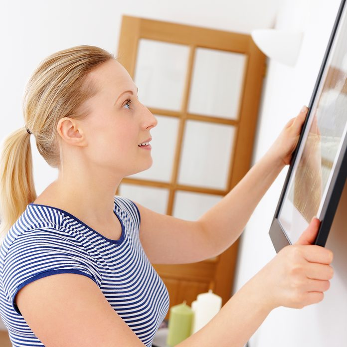 close-up of young attractive woman hanging picture on a wall