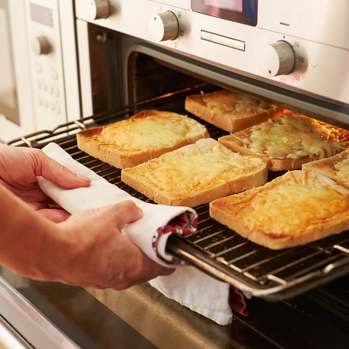 Cheese On Toast Being Grilled In Oven And Taken Out