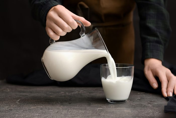 Woman pouring fresh milk from jug into glass on table, an example of food with lactose.