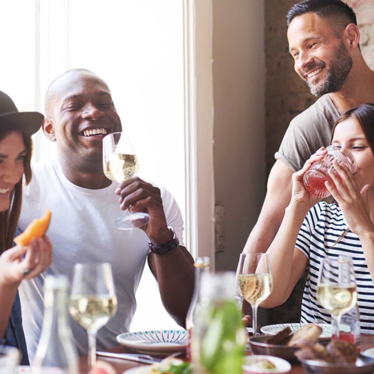 Gathering of four diverse laughing adults enjoying wine and appetizers at lunch with each other at restaurant table beside large bright window; Shutterstock ID 435402382