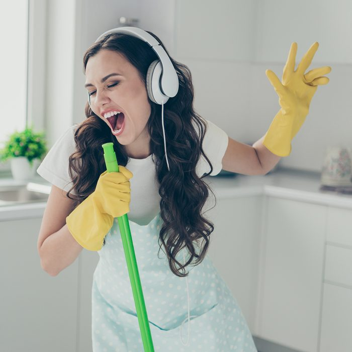 Full length body size portrait of her she nice beautiful lovely cheerful cheery funny wavy-haired house-wife using broom like mic fooling having fun in modern light white interior indoors