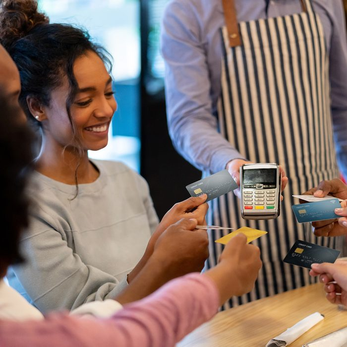 Happy group of friends paying with a credit card at a restaurant and splitting the bill – business concepts. **DESIGN ON CARDS WERE MADE FROM SCRATCH BY US**
