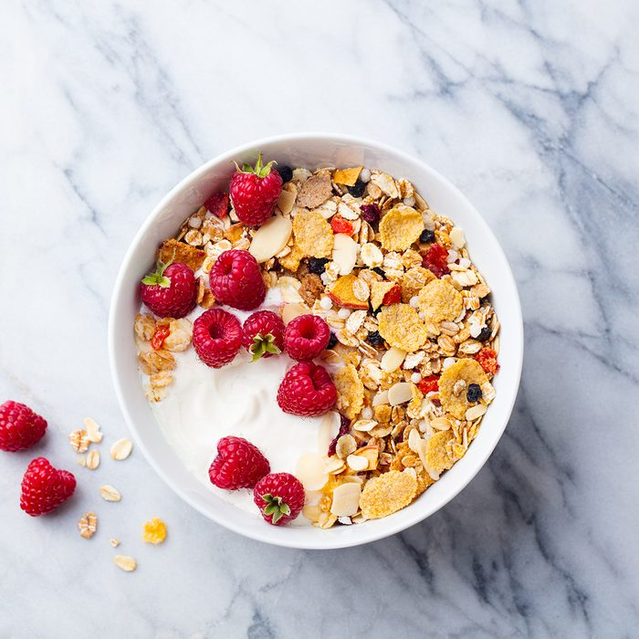 Healthy breakfast. Fresh granola, muesli with yogurt and berries on marble background. Top view