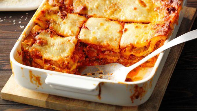 cut lasagna on wooden board metal spoon