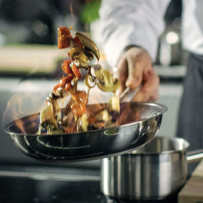Professional Chef Cooks Flambe Style. He Prepares Dish in a Pan with Open Flames. He Works in a Modern Kitchen with Different Ingredients Lying Around.