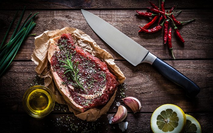 Raw beef steak on butchers paper with a kitchen knife at the right side shot from above on rustic wooden table.