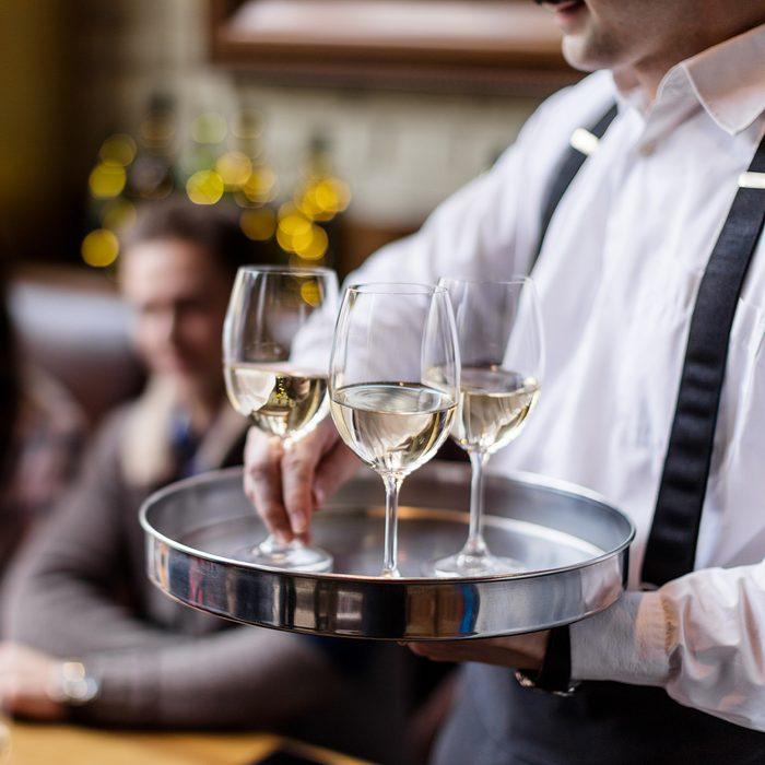 Waiter serving white wine in restaurant