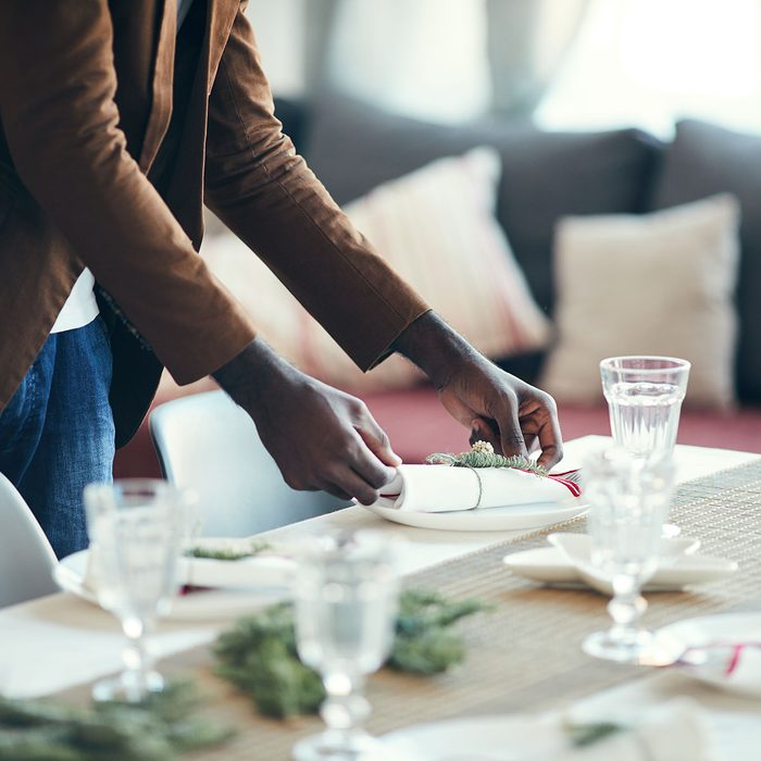 Cropped portrait of young African-American man preparing table setting while decorating dining room for Christmas party at home, copy space; Shutterstock ID 1549665662; Job (TFH, TOH, RD, BNB, CWM, CM): tfh