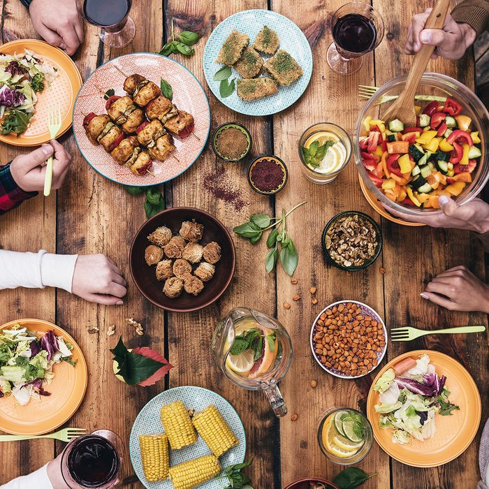 Enjoying dinner together. Top view of four people having dinner together while sitting at the rustic wooden table; Shutterstock ID 323732702; Job (TFH, TOH, RD, BNB, CWM, CM): tfh