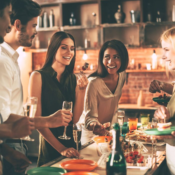 Enjoying home party. Group of cheerful young people enjoying home party with snacks and drinks while communicating on the kitchen ; Shutterstock ID 492008305; Job (TFH, TOH, RD, BNB, CWM, CM): tfh