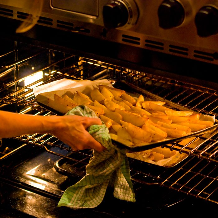 Woman lifting tray out of oven