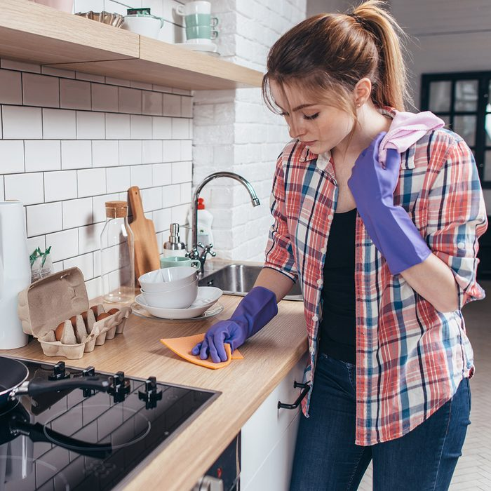 Young woman wiping table in the kitchen