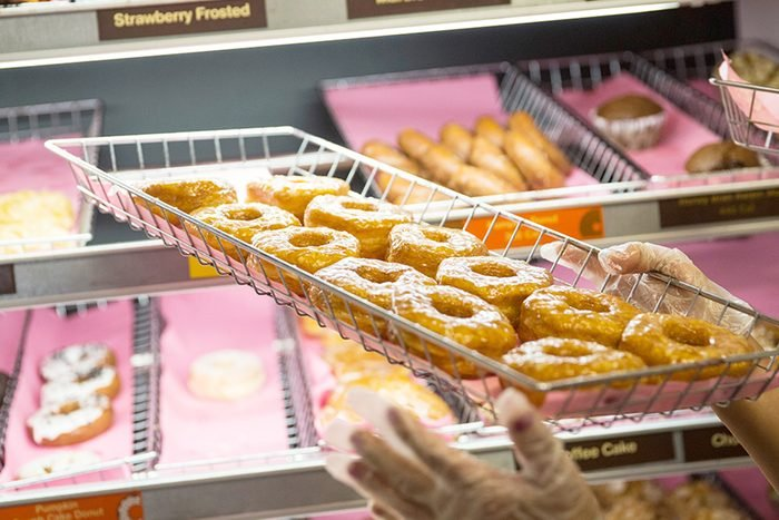 """NEW YORK, NY - NOVEMBER 03: A Dunkin' Donuts employee places a fresh tray of """"croissant doughnuts,"""" on the shelf on November 3, 2014 in New York City. The pastry, which began selling at Dunkin' Donuts two days ago, is based on baker Dominque Ansel's hybrid pastry, the """"cronut,"""" which came to popularity in the summer of 2013. (Photo by Andrew Burton/Getty Images)"""