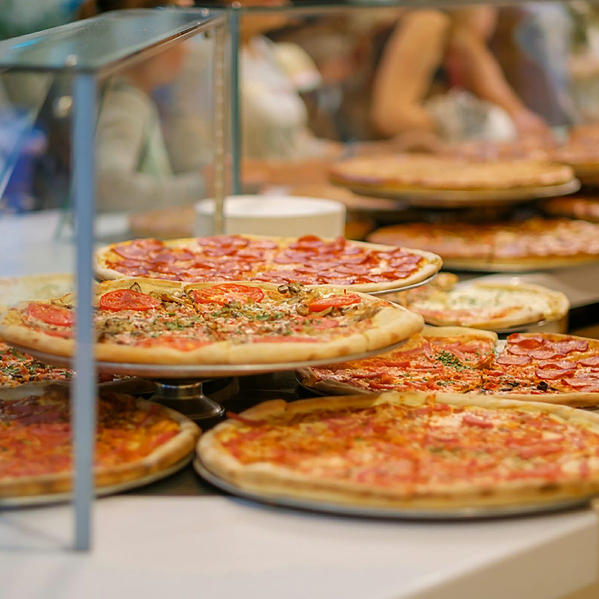 Variety of yummy pizzas under shopping window in pizzeria; Shutterstock ID 676292251