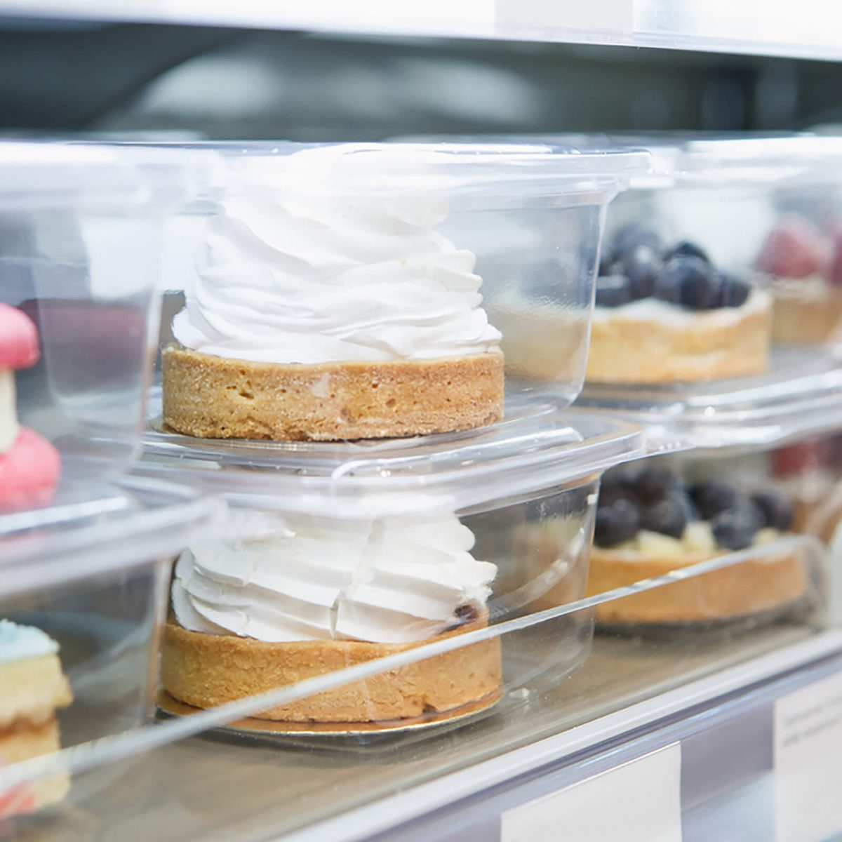 Delicious little cake in refrigerator packed in plastic container.Fresh sweet pastry for coffeebreak.Creamy cakes in freezer.Eat delicious bakery product with cream,sugar.Frozen cup cakes in container; Shutterstock ID 558665518
