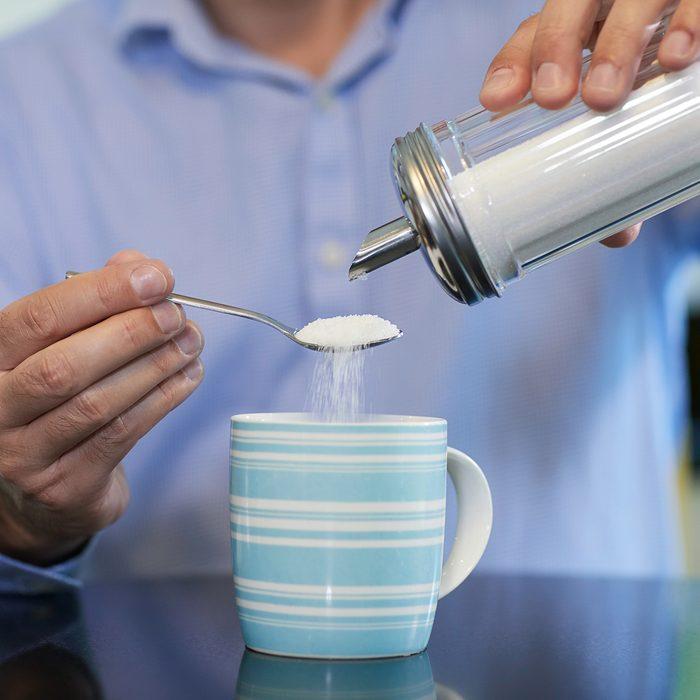 Close Up Of Mature Man Adding Sugar To Hot Drink At Home
