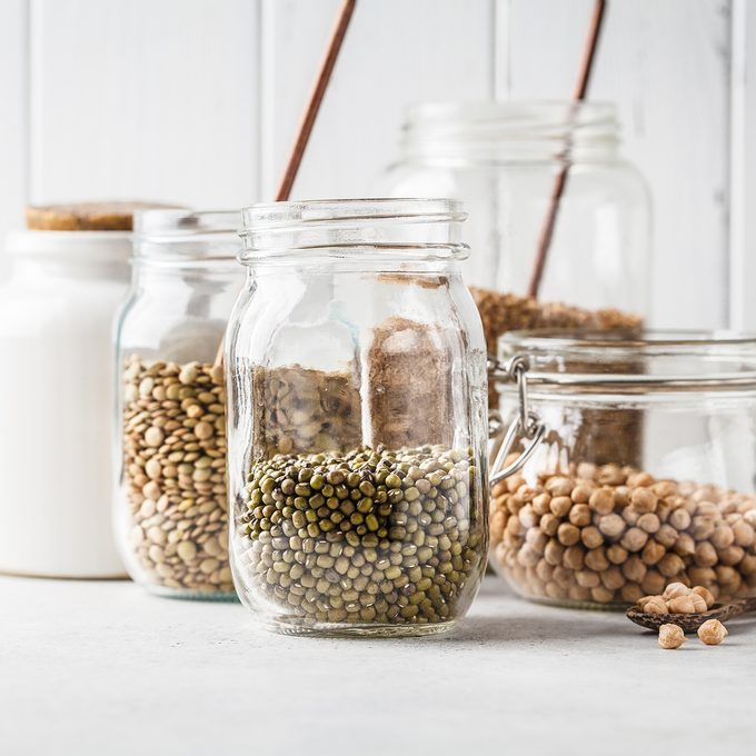 Various legumes: beans, chickpeas, buckwheat, lentils in glass jars on a white background. Healthy vegetarian food, vegetable protein, plant based diet concept.