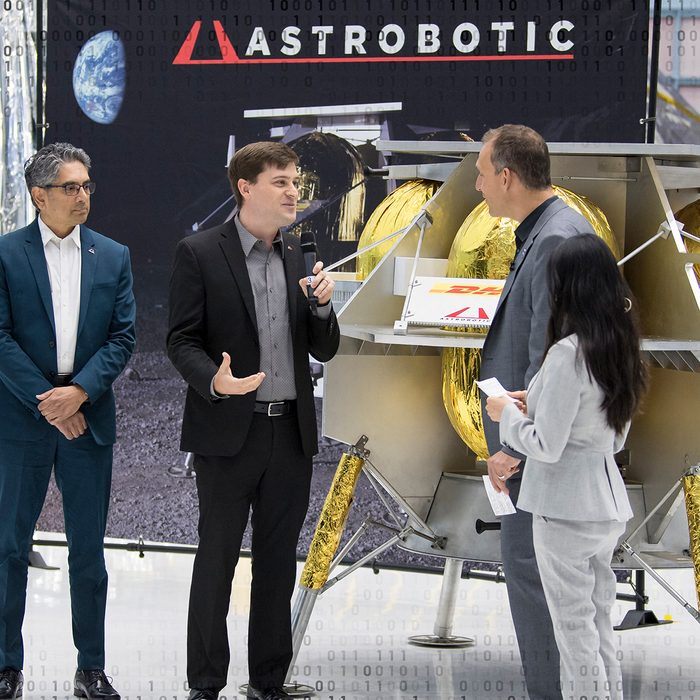 GREENBELT, MARYLAND - MAY 31: In this handout provided by the National Aeronautics and Space Administration (NASA), NASA Associate Administrator, Science Mission Directorate, Thomas Zurbuchen, second from right, speaks to Astrobotic CEO, John Thornton, second from left, and Astrobotic Mission Director, Sharad Bhaskaran, left, about their lunar lander, May 31, 2019, at Goddard Space Flight Center in Maryland. Astrobotic, Intuitive Machines, and Orbit Beyond have been selected to provide the first lunar landers for the Artemis program's lunar surface exploration. (Photo by Aubrey Gemignani-NASA/Getty Images)