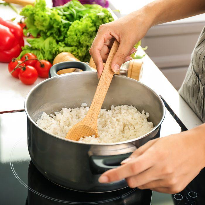 Woman cooking rice in saucepan on stove