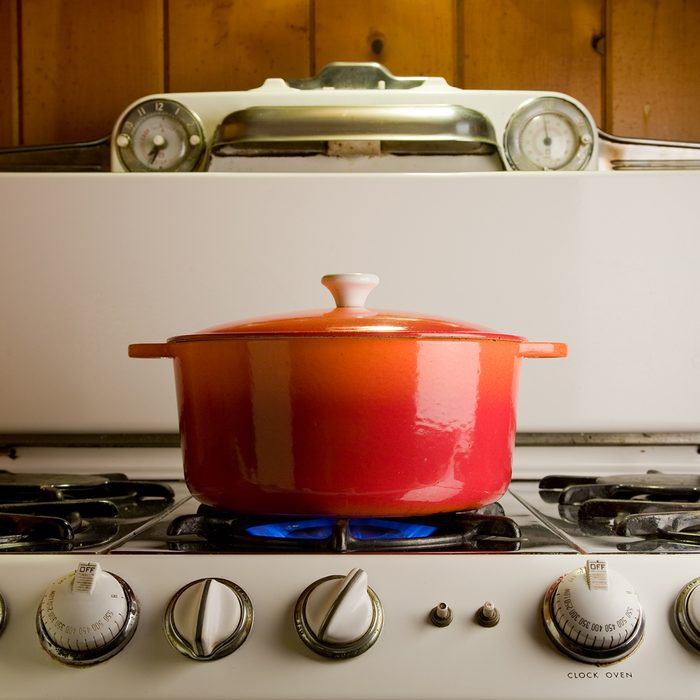 red cast iron pot cooking on antique stove