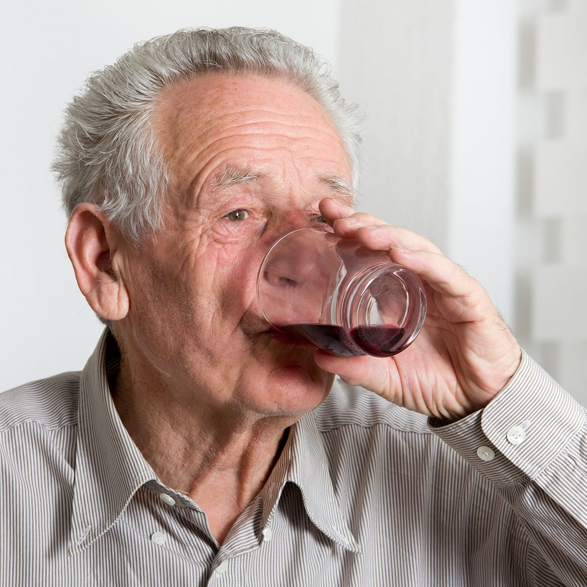 Close up of old man drinking blueberry juice