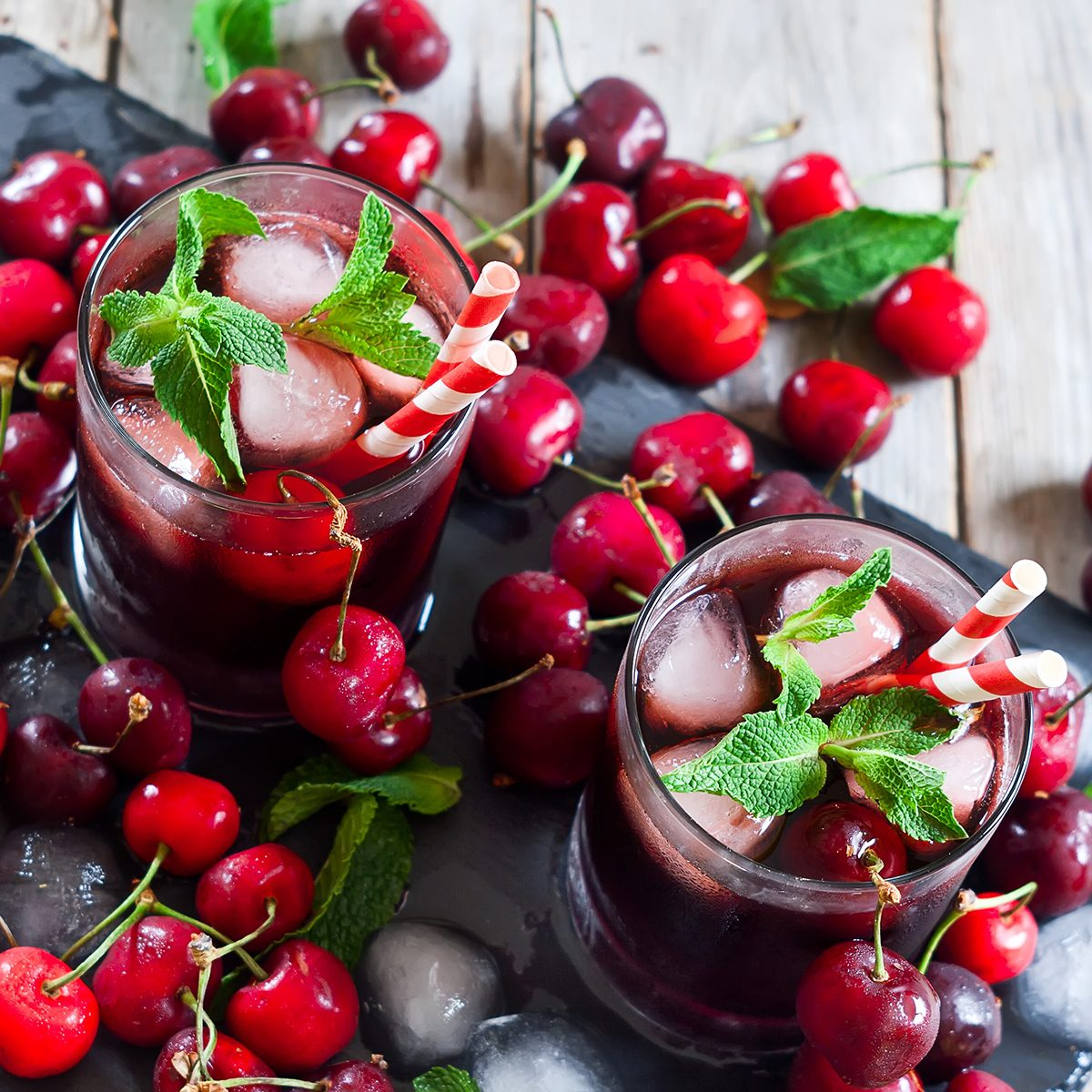 Cherry juice with ice cubes, mint leaves and ripe sweet cherry