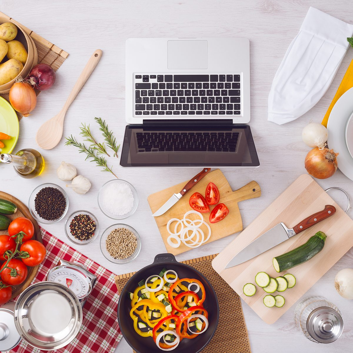 Home kitchen table top view with laptop, food ingredients, raw vegetables, kitchenware and utensils, top view
