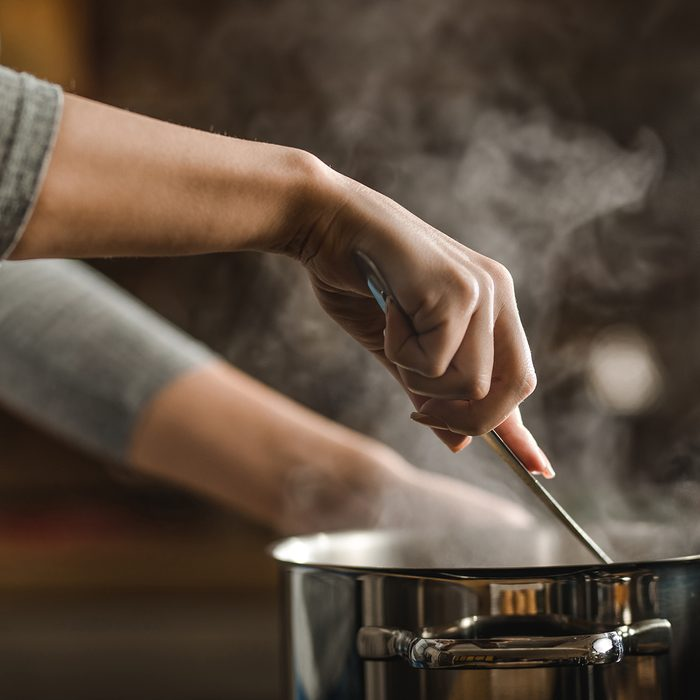 Unrecognizable woman making lunch in the kitchen and stirring soup.
