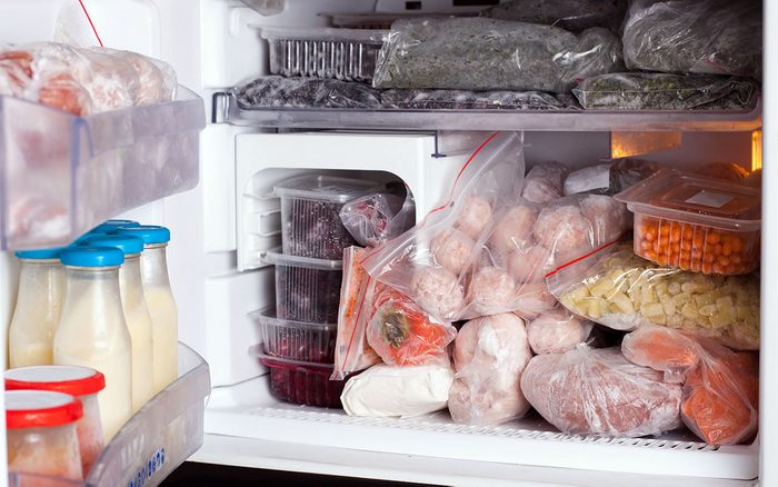 Refrigerator with frozen food (meat, milk, vegetables)