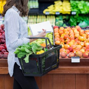 Young woman carries a shopping basket filled with fresh produce. She is shopping for fresh fruit and vegetables in a grocery store.