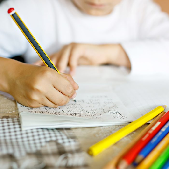 Child doing homework and writing story essay. Elementary or primary school class. Closeup of hands and colorful pencils.