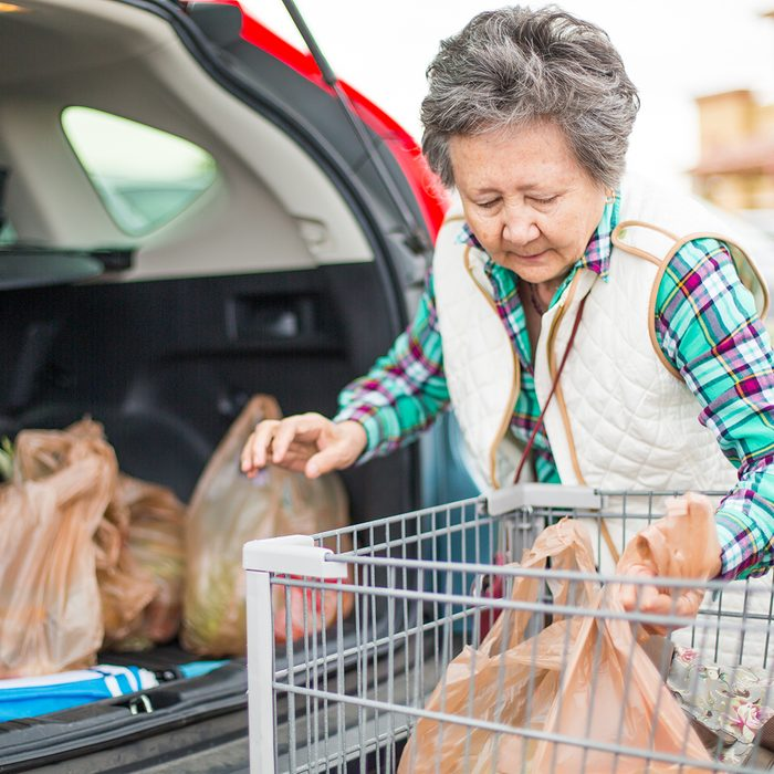 Senior woman loading grocery bags in the trunk of her car.