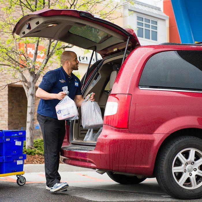 Walmart employee putting groceries into a customer's car