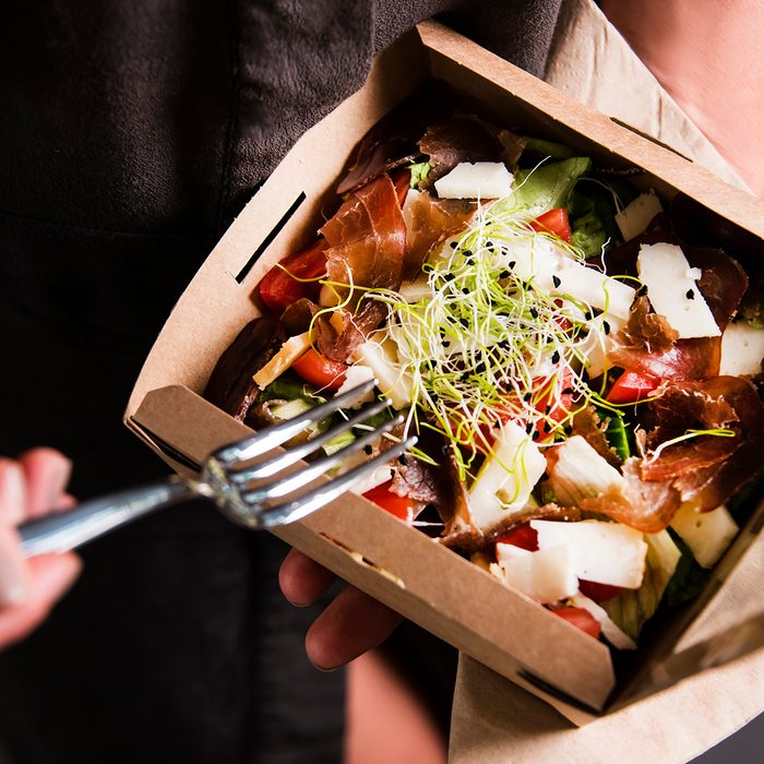 Woman's hand is holding a take away fresh salad in a lunch box. Gourmet conception.