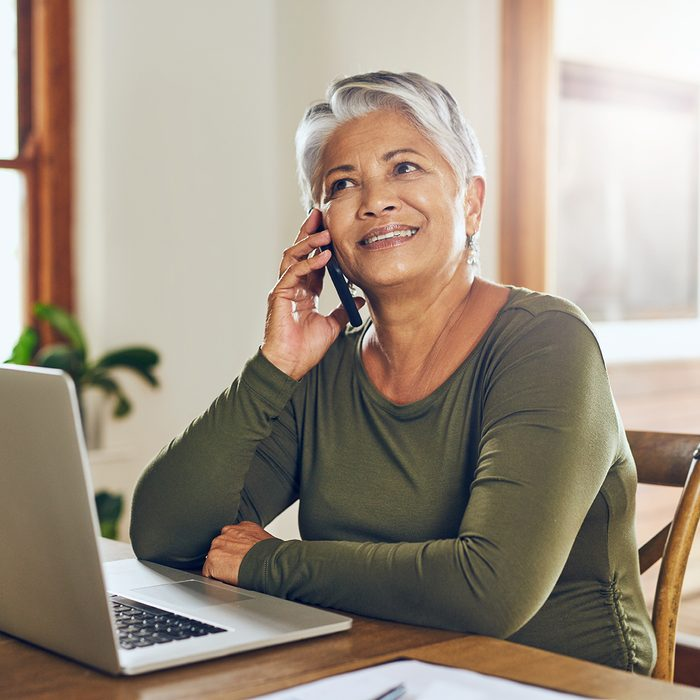Shot of a mature woman talking on a cellphone while working on a laptop at home
