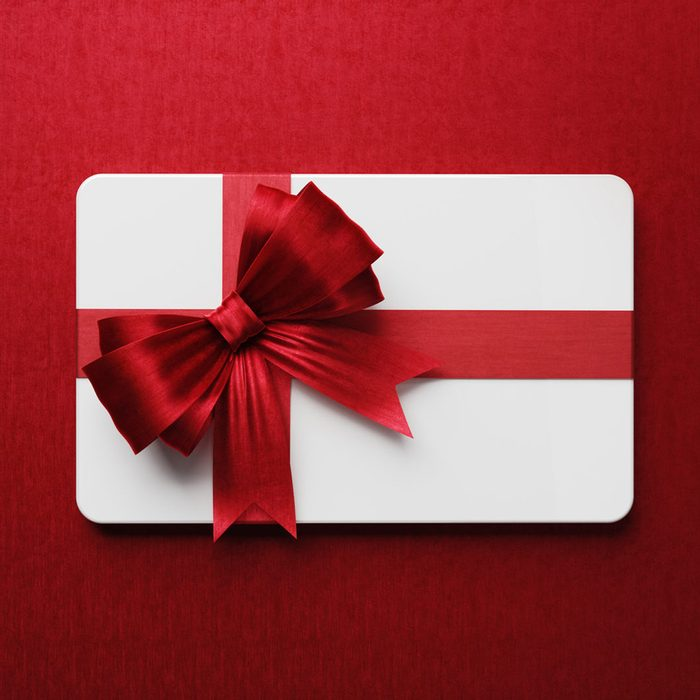 White gift card with red bow tie on red background. Vertical composition with copy space.