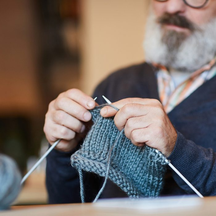 Bearded grandpa knitting warm woolen sweater or other knitwear at leisure