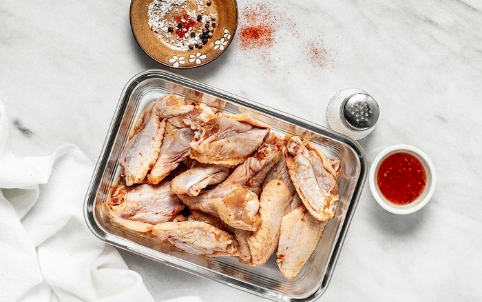 Raw chicken wings in a glass bowl on white background